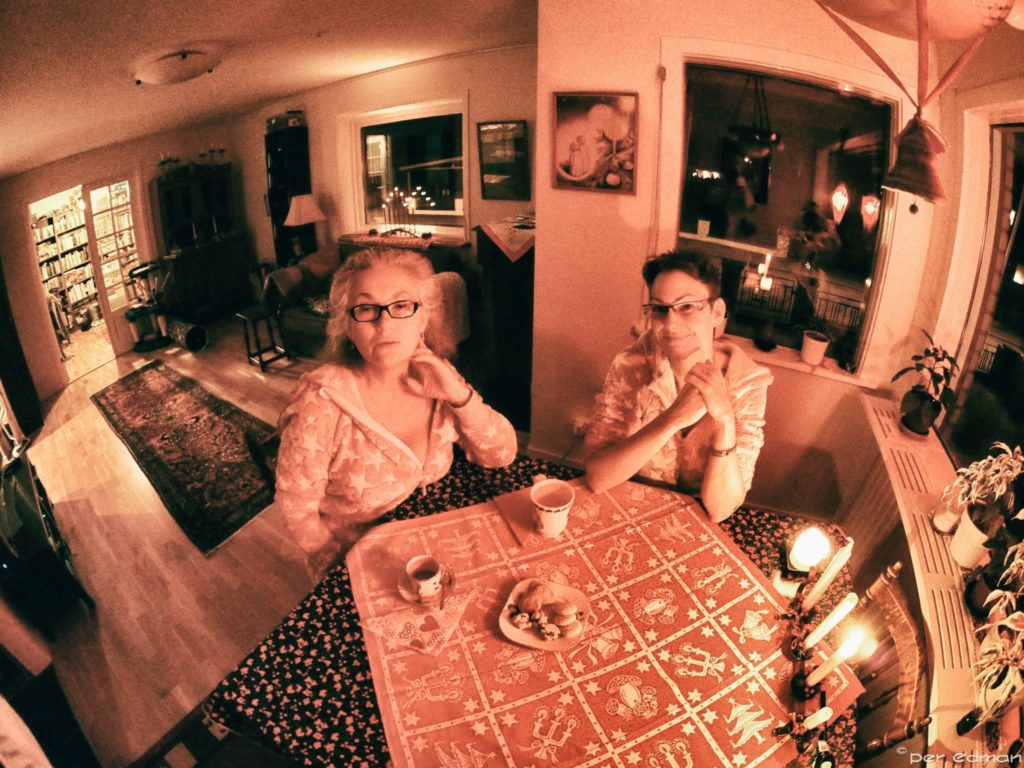 Two women at a table, dressed in onesies. The light is very pinkish red.