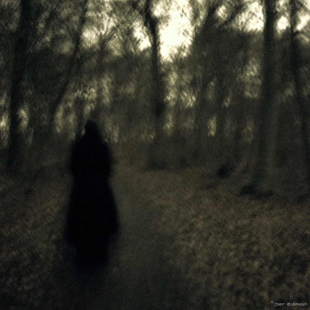 A very dark figure on a dark backdrop.
