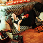 A wide angle shot of Courtnee spreading out on a two-seater couch