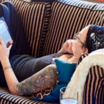 Courtnee lying down on a sofa, reading from her kindle. Her right arm is vividly tattooed.