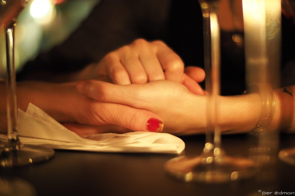 Three hands clasping one another in a soft warm light.